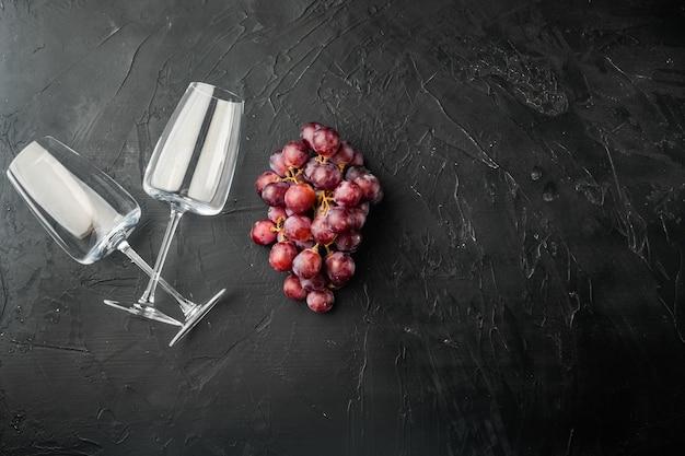 Wijnglazen met druiven set, op zwarte stenen tafel, bovenaanzicht plat lag