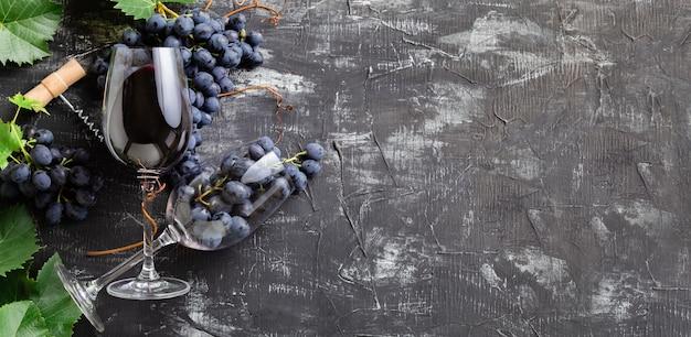 Wijnglazen met rode wijn en druiven. druiventrossen met bladeren en wijnstokken kurken op donkere rustieke betonnen achtergrond. platliggende wijnsamenstelling op zwarte stenen tafel. lange webbanner met kopieerruimte.