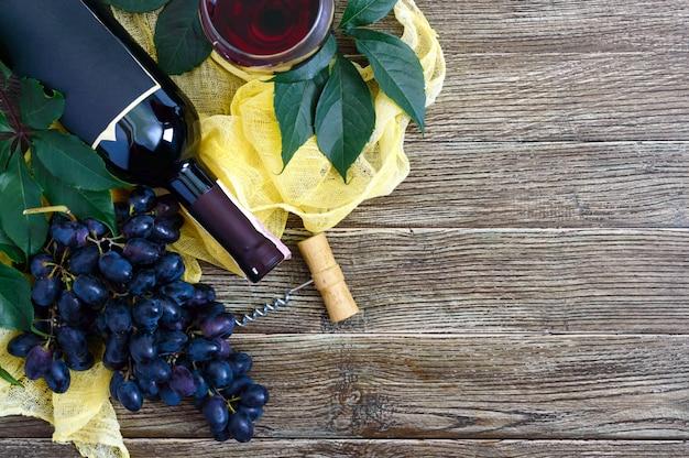 Wijnglazen met rode wijn, fles, kurkentrekker, blauwe druiven, bladeren op een houten tafel.