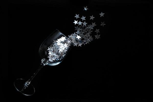 Wijnglazen met zilveren sterconfettien op zwarte achtergrond. plat leggen, bovenaanzicht.