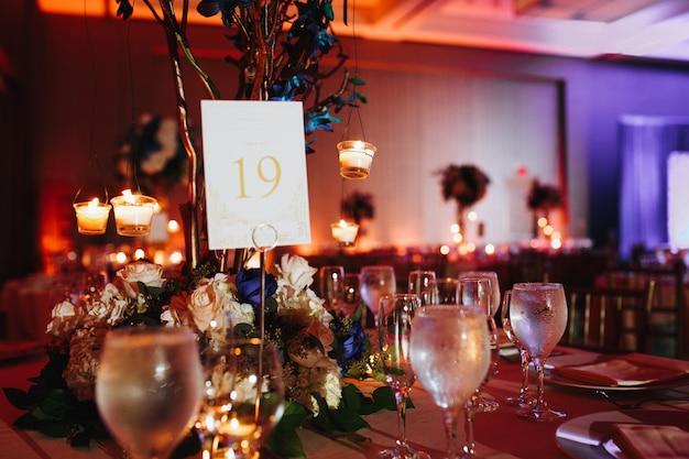 Wijnglazen op de gediende tafel met verlichtingskaarsen en tafelnummer erop