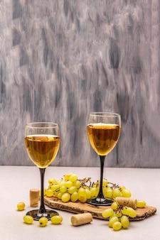 Wijnglazen, verse druiven en kurken op houten snijplank. wijnbar, wijnmakerij, wijnproeverij concept