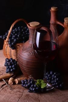 Wijnkelder met wijnglas en rieten mand met druiven
