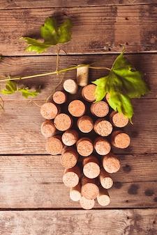 Wijnkurken op houten achtergrondgeluid als druivenvorm met groen blad