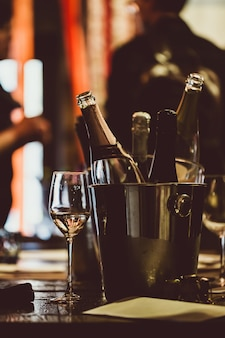Wijnproeven: op een houten tafel staat een zilveren emmer voor het koelen van wijnen met open flessen.