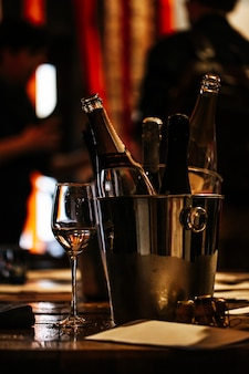 Wijnproeverij: op een houten tafel staat een zilveren emmer voor het koelen van wijnen met open flessen champagne en een glas wijn.
