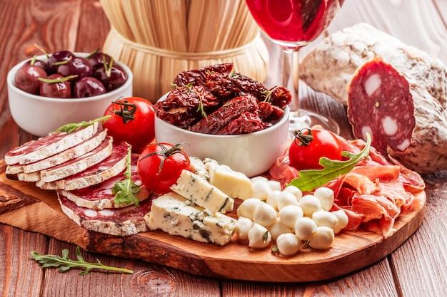 Wijnsnack set. verscheidenheid aan kaas en vlees op donkere achtergrond.