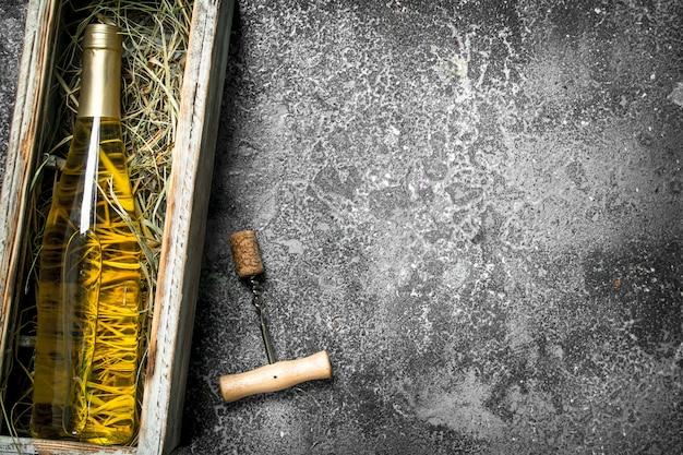 Wijntafel. een fles witte wijn in een oude doos. op een rustieke tafel.
