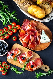 Wijnvoorgerecht op een houten raad. witte wijnkaas, jamon, prosciutto, met salami en olijven op een zwarte achtergrond. versgebakken brood met kaas en wijnsnacks. lekkere feesthapjes