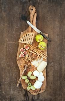 Wijnvoorgerechten op olijf houten dienende raad worden geplaatst over rustieke achtergrond die