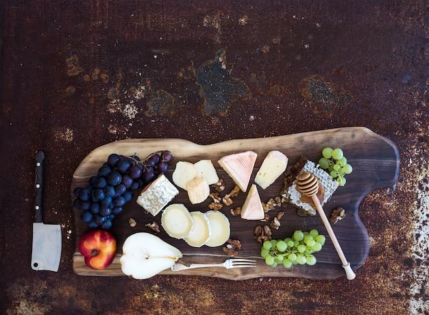 Wijnvoorgerechten set: franse kaas selectie, honingraat, druiven, perzik en walnoten op rustieke houten bord over donkere grunge metaal. bovenaanzicht