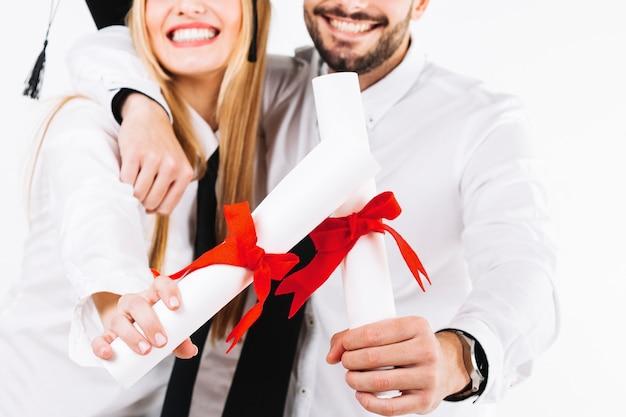 Wijs vrolijke mensen met diploma's bij