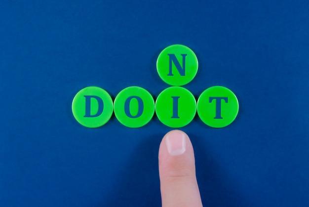 Wijsvinger van een zakenman die letter i duwt in plaats van n om do it-bericht te vormen in plaats van niet.
