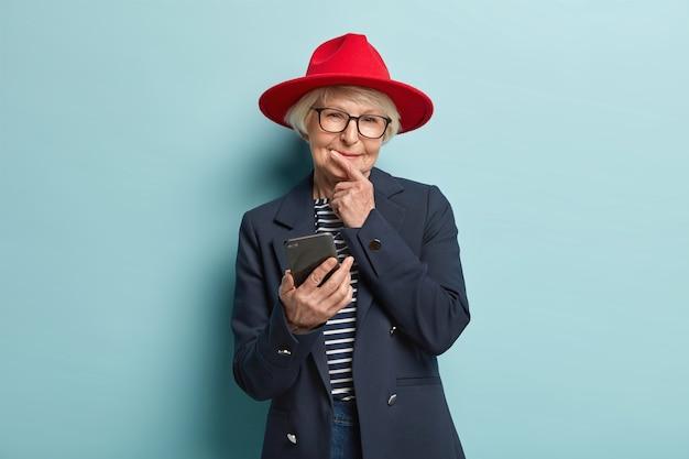 Wijze, bedachtzame, tevreden oudere, gerimpelde vrouw houdt de kin vast, leest de melding, is verbonden met draadloos internet, draagt een rode hoofddeksel en een modieuze jas, krijgt korting op e-mail. mensen, leeftijd, wijsheid