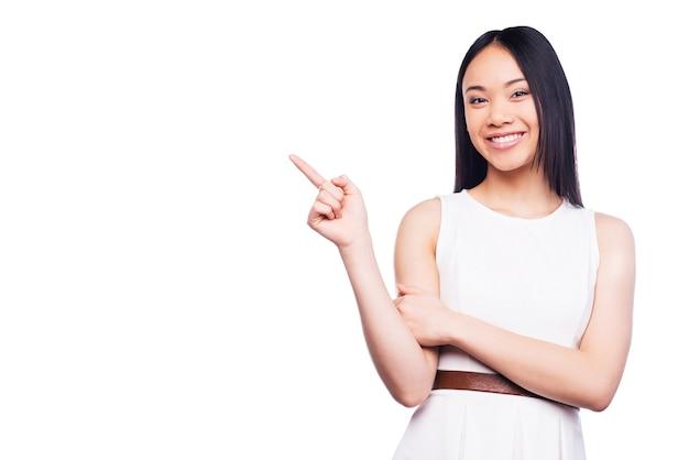 Wijzend exemplaar ruimte. mooie jonge aziatische vrouw die wegwijst en glimlacht terwijl ze tegen een witte achtergrond staat