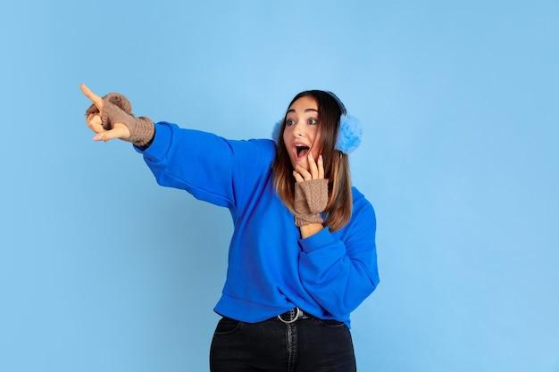 Wijzend. het portret van de kaukasische vrouw op blauwe studioachtergrond. mooi vrouwelijk model in warme kleren. concept van menselijke emoties, gezichtsuitdrukking, verkoop, advertentie. winterstemming, kersttijd, feestdagen.