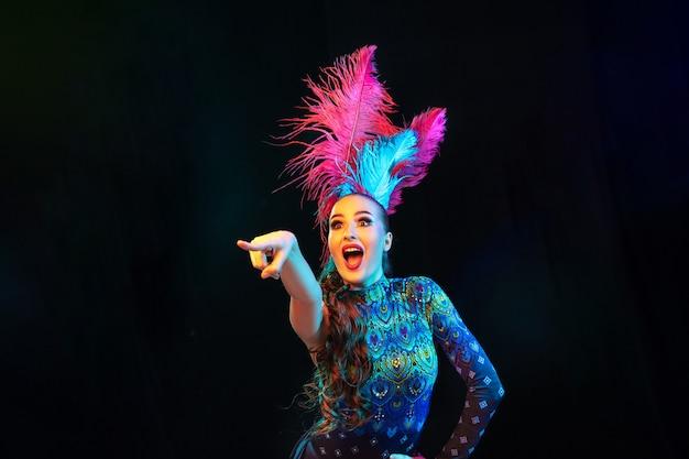 Wijzend. mooie jonge vrouw in carnaval, stijlvol maskeradekostuum met veren op zwarte achtergrond in neonlicht. copyspace voor advertentie. vakantie vieren, dansen, mode. feestelijke tijd, feest.