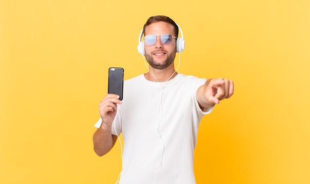 Wijzend naar de camera die jou kiest, muziek luisteren met een koptelefoon en een smartphone