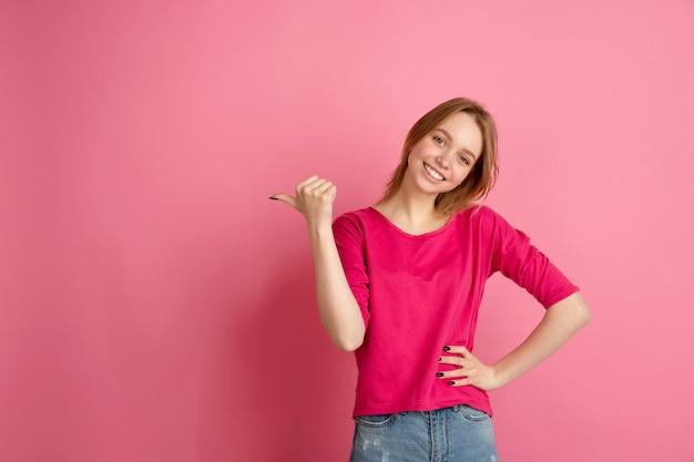 Wijzend naar de zijkant. het portret van de kaukasische jonge vrouw op roze studio