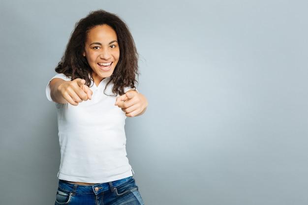 Wijzend naar jou. geweldig buitenlands meisje positiviteit uitdrukken en recht naar de camera kijken terwijl je over een grijze achtergrond staat