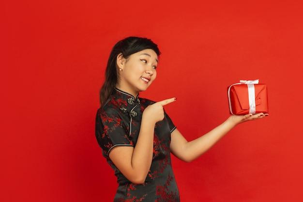 Wijzend op cadeau. gelukkig chinees nieuwjaar 2020. het portret van het aziatische jonge meisje dat op rode achtergrond wordt geïsoleerd. vrouwelijk model in traditionele kleding ziet er gelukkig uit. viering, vakantie, emoties. copyspace.