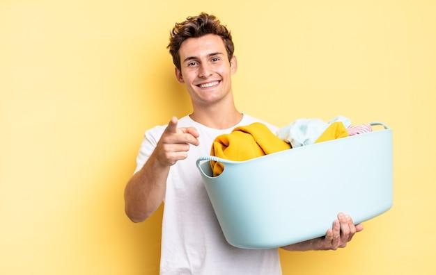 Wijzend op de camera met een tevreden, zelfverzekerde, vriendelijke glimlach, jou kiezen. kleren wassen concept