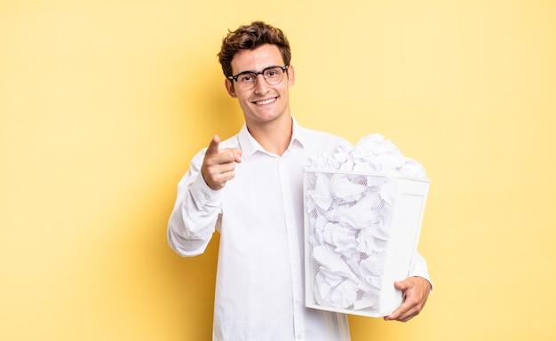 Wijzend op de camera met een tevreden, zelfverzekerde, vriendelijke glimlach, jou kiezen. prullenbak papier concept