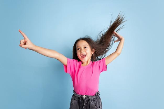 Wijzend op in sprong. het portret van het kaukasische meisje op blauwe muur. mooi vrouwelijk model in roze overhemd.