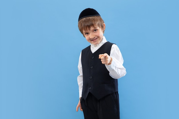 Wijzend. portret van een jonge orthodoxe joodse jongen geïsoleerd op blauwe muur. purim, zaken, festival, vakantie, jeugd, viering pesach of pesach, jodendom, religieconcept.