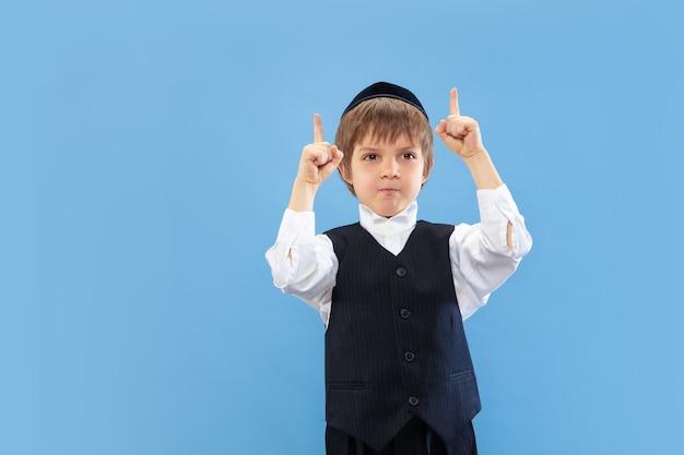Wijzend. portret van een jonge orthodoxe joodse jongen geïsoleerd op blauwe studio muur.