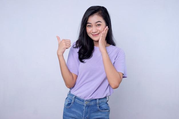 Wijzende duimen omhoog. goed uitziende ondersteunende en charismatische aziatische vriendin met zwart haar met een leuk en geweldig gebaar op een witte muur