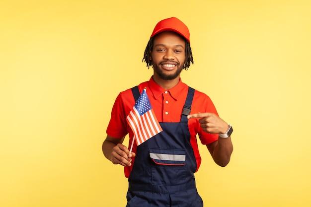 Wijzende vinger naar de amerikaanse vlag in zijn hand en kijken naar de camera met een brede glimlach