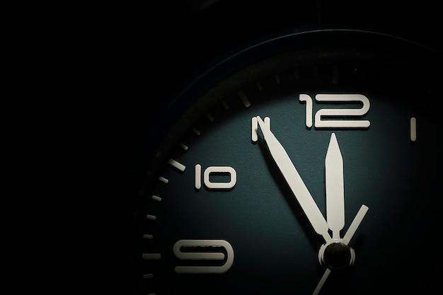 Wijzerplaat van een klok met vijf minuten voor twaalf