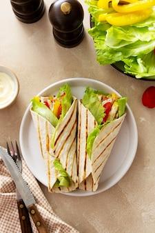 Wikkel burrito sandwich of kebab met flatbread met groenten en wit vlees. heerlijk gezond eten, snacks om mee te nemen