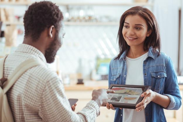 Wil deze. mooie jonge vrouw die een tablet met cafémenu vasthoudt en aan haar vriend laat zien terwijl de man naar het gerecht van zijn keuze wijst