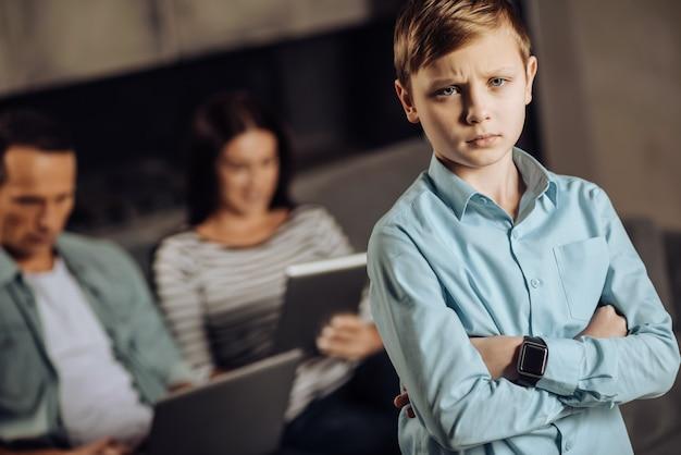 Wil geliefd worden. boos pre-tienerjongen pruilen, teleurgesteld zijn door het gebrek aan aandacht van zijn ouders terwijl de ouders op de bank zitten en aan hun laptop vastgelijmd zijn