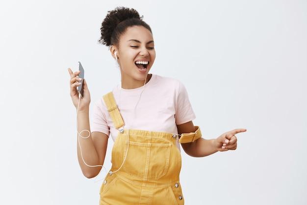 Wil je met iemand dansen. portret van vrolijke gelukkig aantrekkelijke afro-amerikaanse vrouw in gele stijlvolle tuinbroek, bewegen in het ritme van muziek, liedjes luisteren in oortelefoons, mobiele telefoon houden