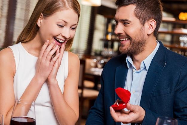 Wil je met me trouwen? knappe jonge man die een voorstel doet terwijl hij een verlovingsring geeft aan zijn vriendin in restaurant