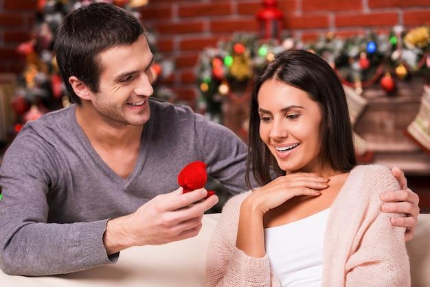 Wil je met me trouwen? knappe jonge man die een voorstel doet terwijl hij een verlovingsring geeft aan zijn vriendin met kerstversiering op de achtergrond