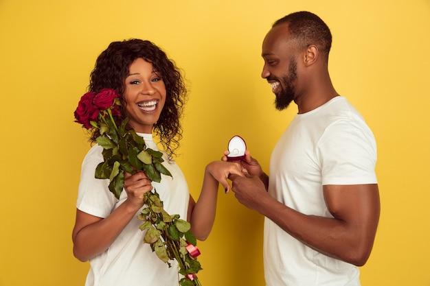 Wil je met me trouwen. valentijnsdagviering, gelukkig afrikaans-amerikaans paar dat op gele studioachtergrond wordt geïsoleerd. concept van menselijke emoties, gezichtsuitdrukking, liefde, relaties, romantische vakanties.