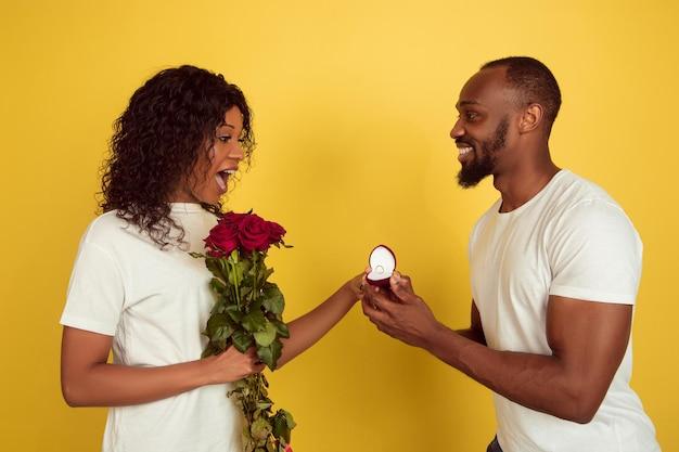 Wil je met me trouwen. valentijnsdagviering, gelukkig afrikaans-amerikaans paar dat op gele studioachtergrond wordt geïsoleerd.