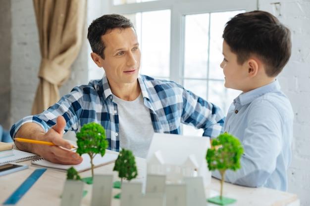 Wil meer weten. aangename pre-tienerjongen die zijn vader vraagt naar zijn werk als architect, geïnteresseerd is in zijn recente project van ecostad, terwijl de man gretig vertelt