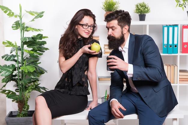Wil wat. sexy vrouw behandelt bebaarde man naar appel. zakelijk stel heeft een snackpauze op kantoor. gezonde natuurlijke snack voor op het werk. vitamine snacks. makkelijke en lekkere kantoorsnack. eet gezond op het werk.