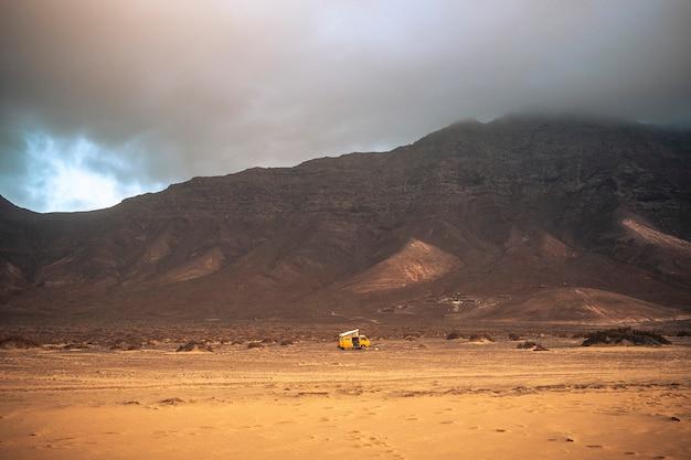 Wild en vrij eenzaam kamperen met oud vintage schilderachtig geel busje alleen geparkeerd met strand op de voorgrond en bergen met wolken in backgorund