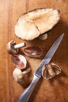 Wild gefoerageerde champignons en mes op een houten snijplank