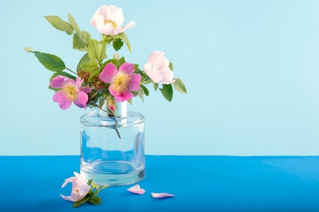 Wild roze bloemen in een glazen vaas