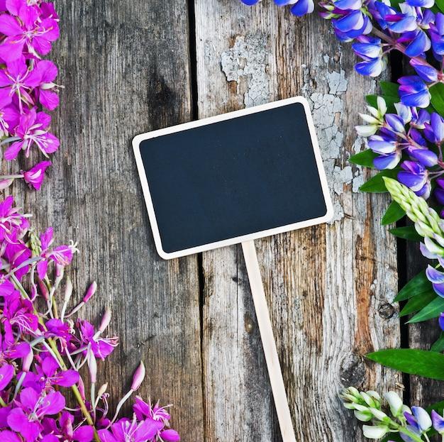 Wilde bloemen en een zwarte bord