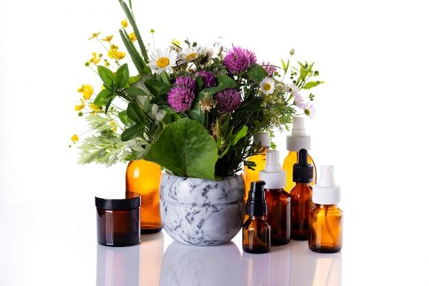 Wilde bloemen in een marmeren vijzel en medicijnfles met etherische olie, cosmetische oliën, aromatherapie, fytotherapie, alternatieve geneeswijzen, natuurlijke huidverzorging.