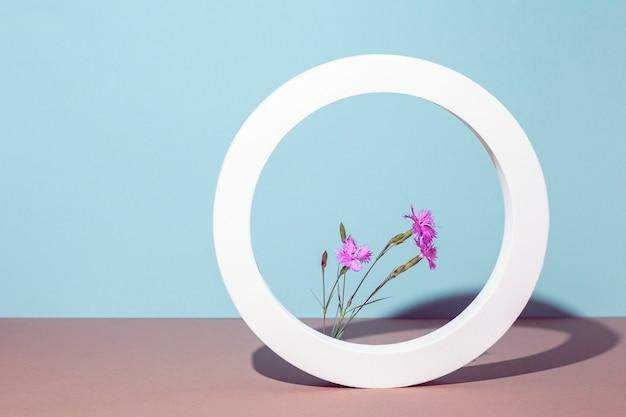 Wilde bloemen in een rond wit frame, presentatiepodium op een blauwe achtergrond.