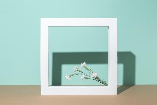 Wilde bloemen in een vierkant frame, een presentatiepodium op een turquoise achtergrond.